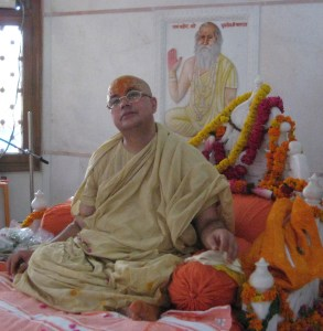 Shri Sadgurudev Ji Maharaj enthroned on the Vyasasan, behind which Shri Param Gurudev Maharaj is continuously giving him blessings.