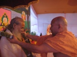 Jagadguru Nimbarkacharya Shri Shriji Maharaj being welcomed on-stage by Shri Sadgurudev Ji Maharaj with a garland