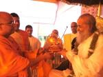 Shri Sadgurudevji Maharaj offering Jagadguru Nimbarkacharya Shri Shriji Maharaj a commemorative Sudarshan Chakra